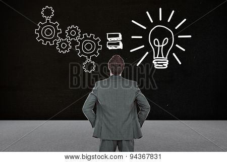 Businessman standing with hands on hips against black room