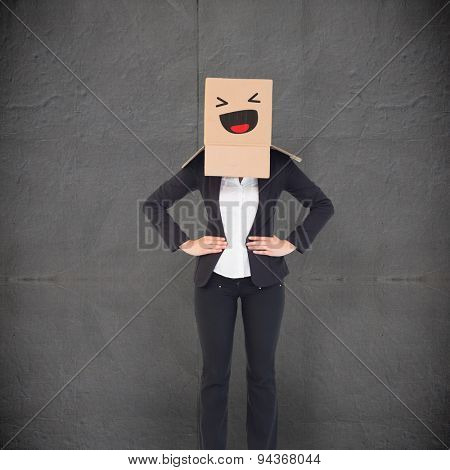 Businesswoman with box over head against grey concrete tile