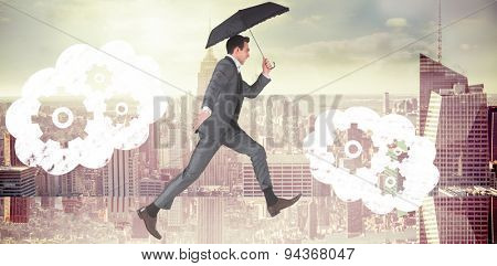 Businessman jumping holding an umbrella against room with large window looking on city
