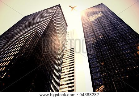 Lens flare against low angle view of skyscrapers