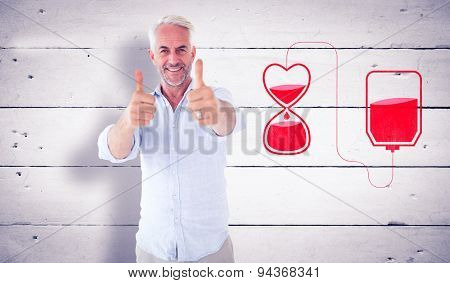 Smiling man showing thumbs up to camera against white wood