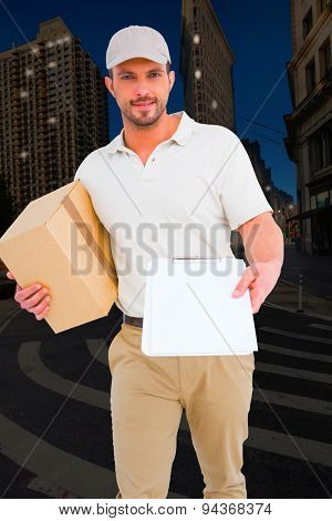 Delivery man with cardboard box showing clipboard against city at night