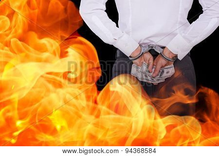 Businessman in handcuffs holding bribe against black