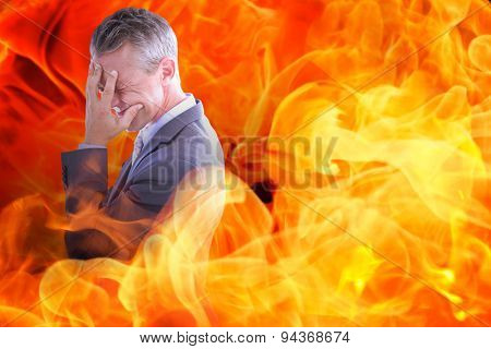 Businessman with headache against fire