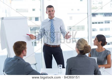 Manager presenting whiteboard to his colleagues in the office