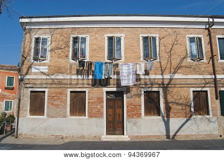 Exterior of the facade of a residential building with washed clothes hanging outside, Murano, Italy.