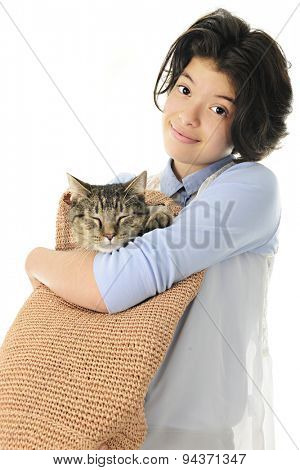 An attractive young teen happily carrying her sleeping cat in a woven shoulder bag. Focus is on the girl.  On a white background.