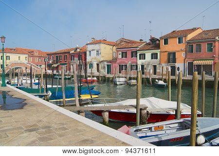 View to the channel boats and buildings at the street in Murano, Italy.