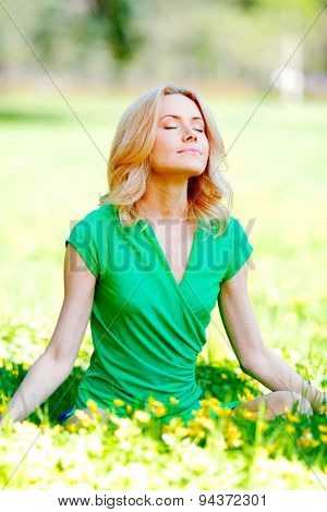 Beautiful young blond woman sitting on grass in park and enjoyng flowers