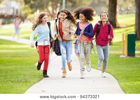 Group Of Young Girls Running Towards Camera In Park