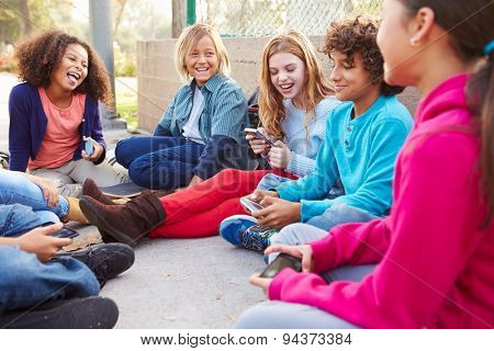 Group Of Young Children Hanging Out In Playground