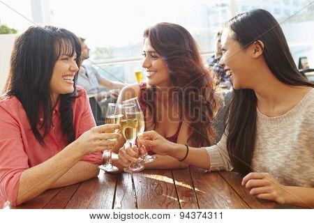 Three Female Friends Enjoying Drink At Outdoor Rooftop Bar