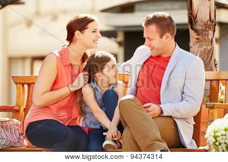 Young Family Sitting On Seat In Mall Together