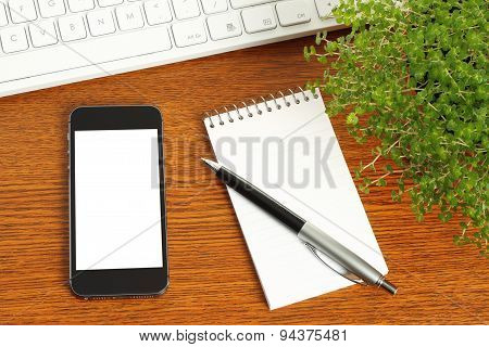 Smart phone keyboard notepad pen and green plant