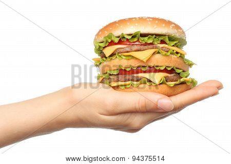 Hand holds big hamburger