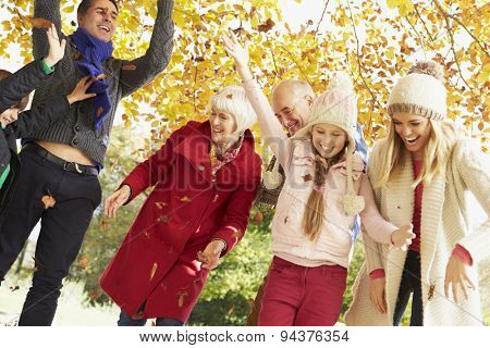 Multl Generation Family Throwing Leaves In Autumn Garden