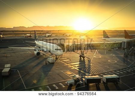 Airplane At The Terminal Gate Ready For Takeoff - Modern International Airport During Sunset