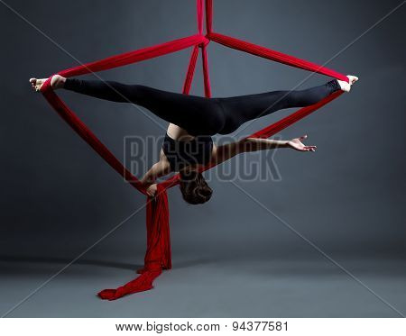 Studio shot of acrobat performs on hanging ribbons