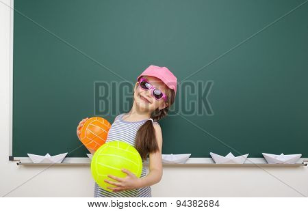 Schoolgirl with ball near the school board