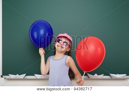 Schoolgirl with balloon near the school board