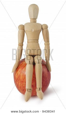 The Wooden Mannequin Sits On A Ripe Apple