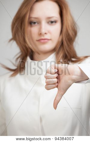 Business woman in white jacket showing thumb down