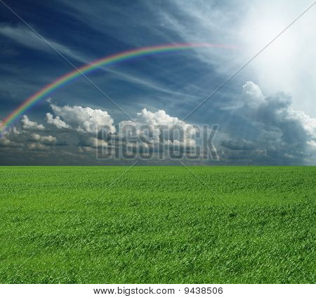 Green Grass And Blue Cloudly Sky With Rainbow