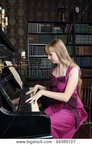Young Woman Plays Piano In Room With Bookshelves And Brown Wallpapers