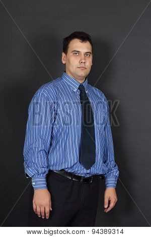 Beautiful Young Serious Man In Tie And Blue Shirt Stands In Black Studio