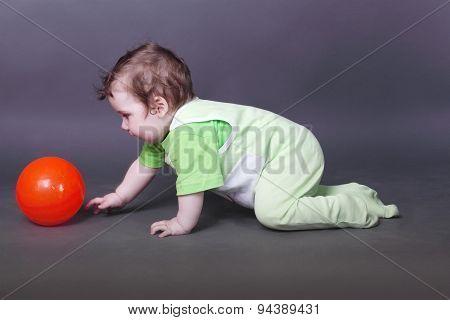 Handsome Little Baby Boy In Green Crawls On Floor For Ball In Grey Studio