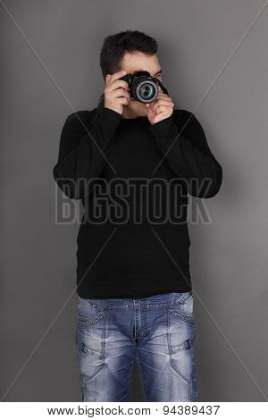 Handsome Young Man In Jeans With Modern Camera Shoots In Grey Studio