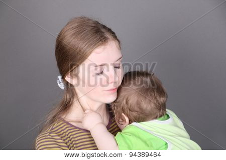 Pretty Young Mother Holds Her Little Baby Son In Green In Grey Studio