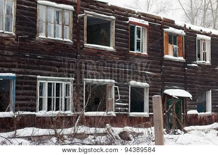 Abandoned Wooden House Made Of Logs During Snowfall On Winter Day