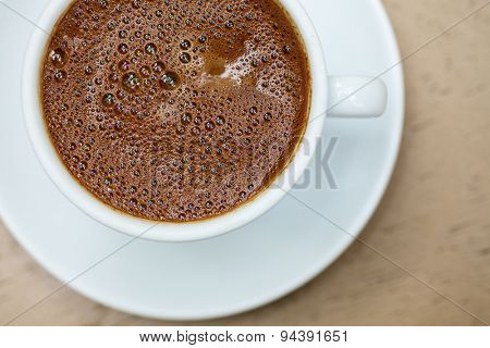 Top view of white cup with frothy greek coffee on a wooden table