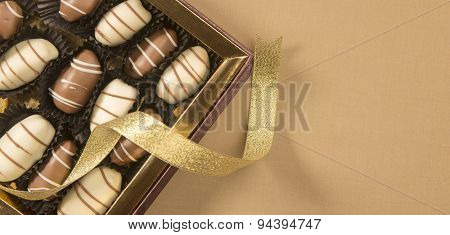 Fine date chocolates in a golden box with loose ribbon wrapped around.