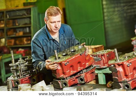 industrial worker assembler with gearbox units at manufacture workshop