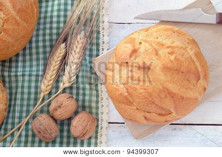 Traditional bread next to ears (wheat) and some nuts