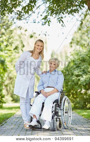 Happy nurse and senior woman in a wheelchair looking at camera in park