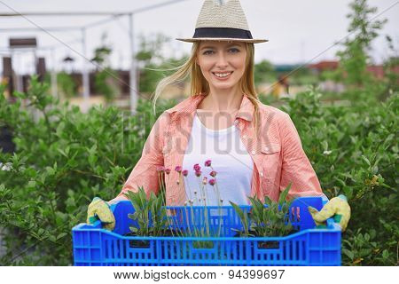 Pretty farmer with floral seedlings looking at camera