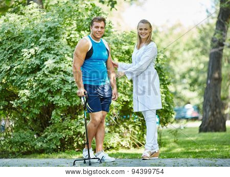 Happy nurse supporting young man with walker while both looking at camera outdoors