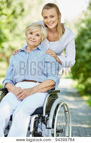 Young caregiver and disabled mature female in a wheelchair looking at camera