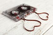 pic of heart sounds  - Audio cassette with magnetic tape in shape of hearts on wooden background - JPG