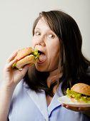 stock photo of greedy  - fat white woman having choice between hamburger and salad greedy - JPG