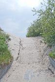 image of pedestrians  - Pedestrian beach boardwalk with sand and sky in Halland Sweden - JPG
