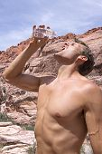 picture of tilt  - Muscular shirtless Caucasian man tilts back head and pours drinking water into mouth from plastic bottle while hiking in Red Rock Canyon desert in Las Vegas on hot sunny day - JPG