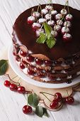 stock photo of icing  - Big cherry cake with chocolate icing on a plate close - JPG
