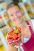 foto of strawberry blonde  - Supermarket worker holding some strawberries - JPG