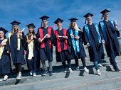 stock photo of graduation  - young graduates students group  standing in front of university building on graduation day - JPG