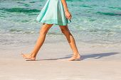 stock photo of legs feet  - Sexy woman dressed with green skirt walking bare foot on the beach shore - JPG