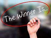 stock photo of winner  - Man Hand writing The Winner Is - JPG